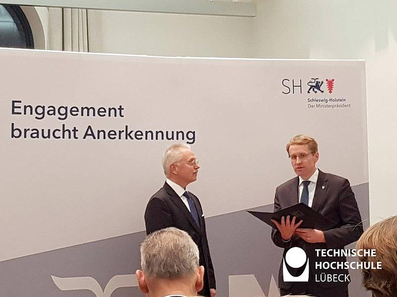 Ministerpräsident Daniel Günther, Schleswig-Holstein, zeichnet Prof. Dr. Rolf Granow (links) mit dem Verdienstorden des Landes aus. (Foto: Arne Welsch, TH Lübeck)