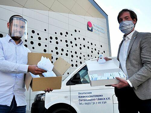 Maschinenbauingenieur Felix Harden, TH Lübeck (links) übergibt erste Masken als Spende an Nicola Leuschner, Geschäftsführer des Kinderschutzbundes Ortsverband Lübeck. Foto: TH Lübeck