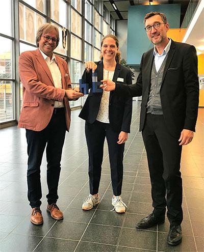 Die Vizepräsidenten Prof. Stefan Fischer, Universität zu Lübeck, und Prof. Frank Schwartze, Technische Hochschule Lübeck, halten gemeinsam mit Anna Lena Paape, Geschäftsführerin der Campusgeschäftsstelle, den neuen Campusnamen in den Händen: Hanse Innovation Campus Lübeck, kurz HIC Lübeck.